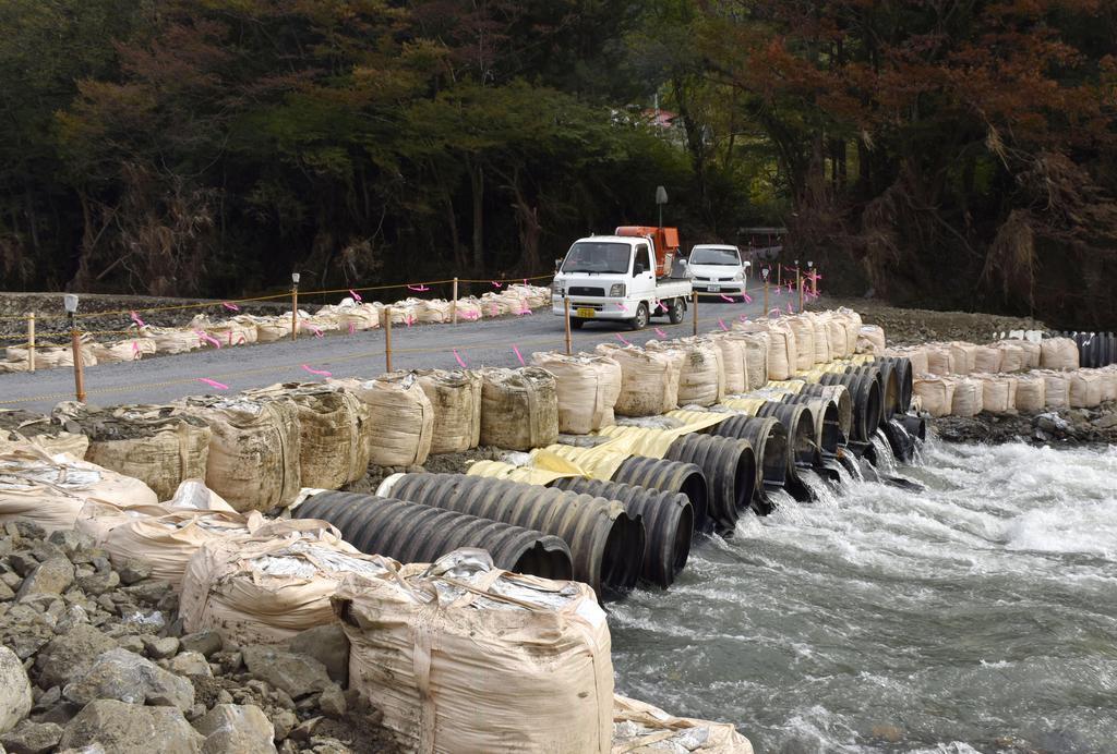 福島県矢祭町で開通した応急措置の橋を通行する車両=3日