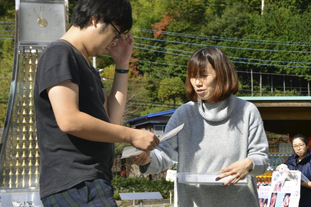「道の駅どうし」で小倉美咲さんの情報提供を呼び掛けるチラシを配る母とも子さん(右)=4日、山梨県道志村
