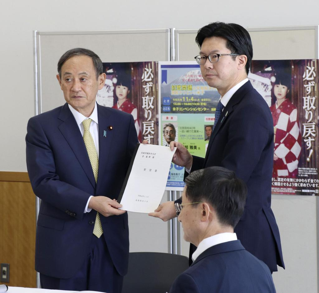 菅官房長官(左)に拉致問題の解決を要望する文書を手渡す伊木隆司米子市長=4日、鳥取県米子市