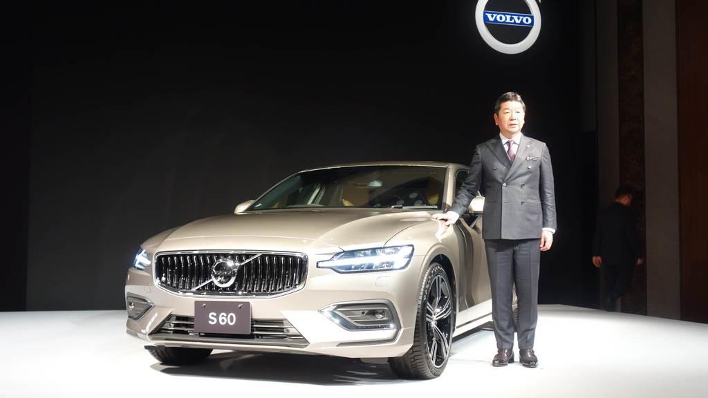 日本で8年ぶりに全面改良発売されたボルボのセダン「S60」とボルボ・カー・ジャパンの木村隆之社長=5日、東京都港区