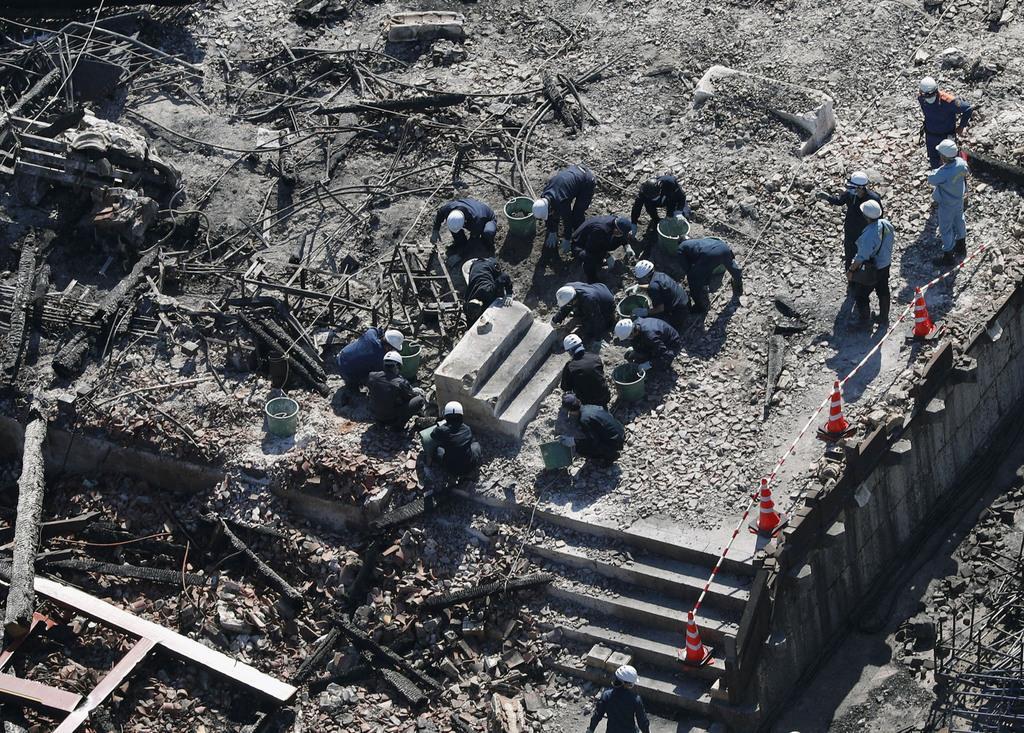 火災のあった首里城で、焼失した正殿を調べる沖縄県警の捜査員ら=2日午前11時7分、那覇市(共同通信社ヘリから)