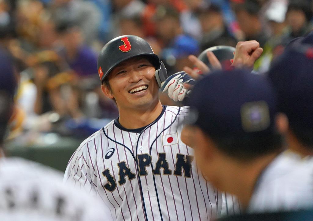 8回、犠飛を放った鈴木誠也はベンチ前でナインとタッチを交わす=桃園国際野球場(長尾みなみ撮影)
