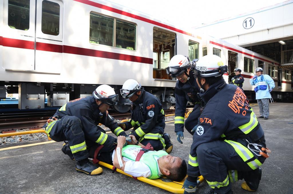 負傷した乗客役を搬送する消防隊員ら=大阪府吹田市