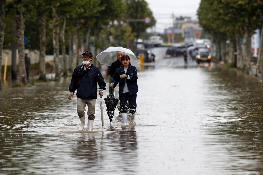 台風19号の影響で冠水した郡山中央工業団地の道路を歩く人たち=10月14日、福島県郡山市