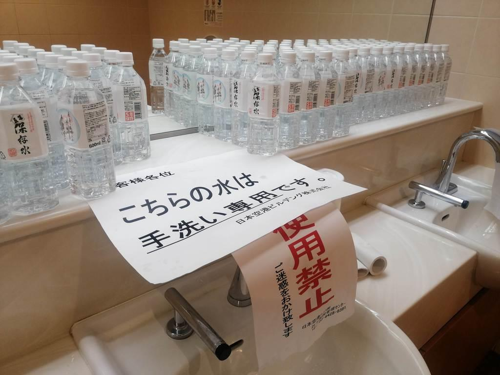 断水の影響で使用禁止となった女子トイレの手洗い場。手洗い用のペットボトルが置かれた=6日、羽田空港第2ターミナル