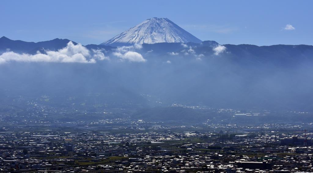 甲府盆地の向こうに浮かび上がった雪化粧した富士山=10月23日午前、甲府市愛宕町から(渡辺浩撮影)