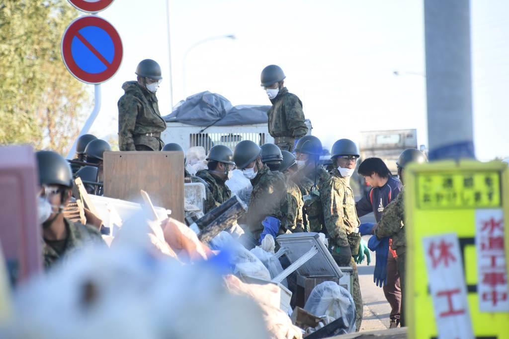 阿武隈川近くでは、道路沿いに積まれた災害ごみを自衛隊員が撤去していた=11月3日、福島県郡山市(吉原実撮影)