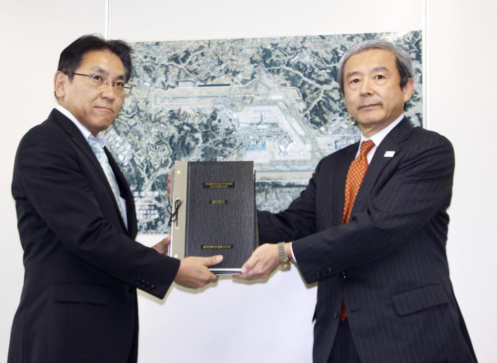 成田空港の機能強化に向けた許可申請を、国交省の担当者に提出するNAAの田村明比古社長(右)=7日、東京・霞が関