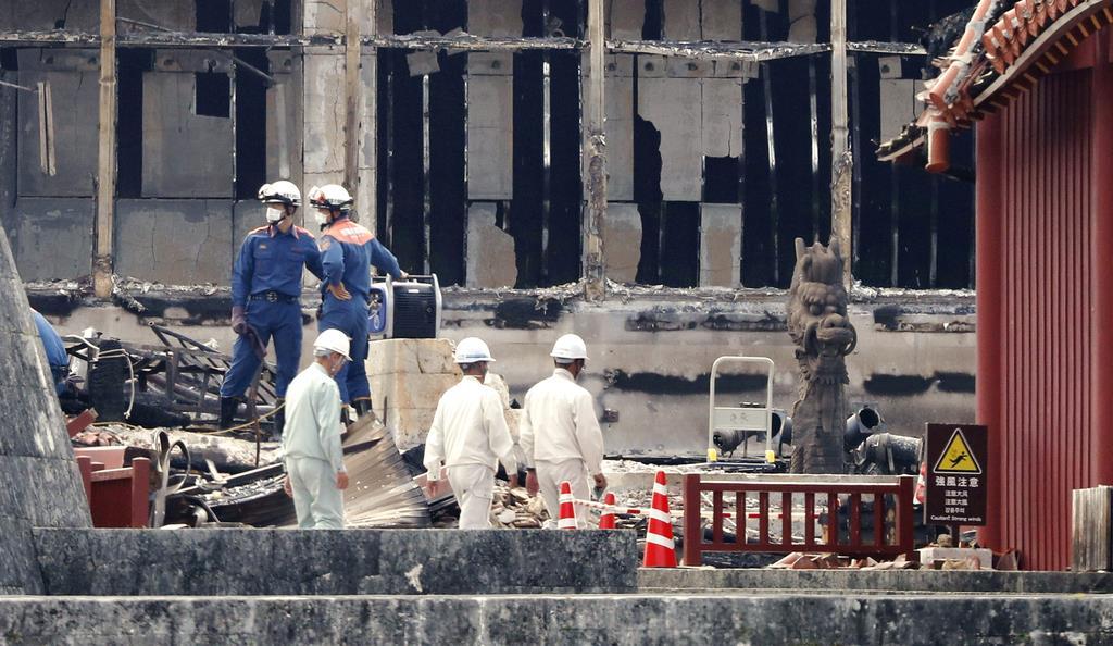 火災で焼失した首里城の正殿を調べる消防隊員ら=5日午後、那覇市