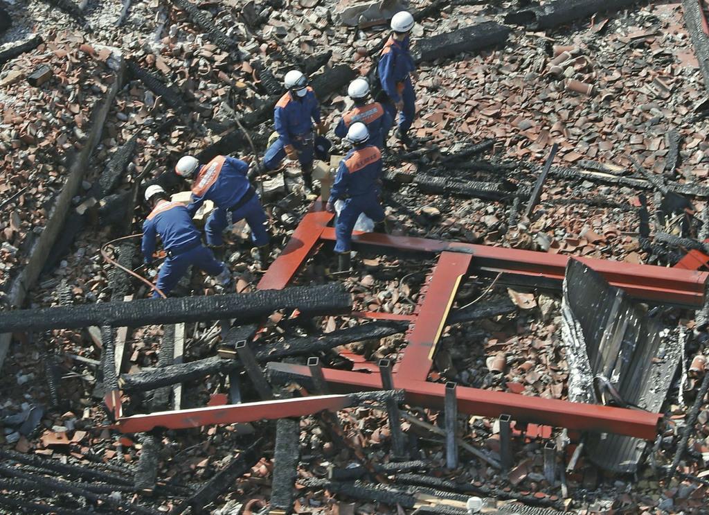 火災で焼失した首里城の正殿付近を調べる沖縄県警の捜査員ら=1日午後0時31分、那覇市(共同通信社ヘリから)