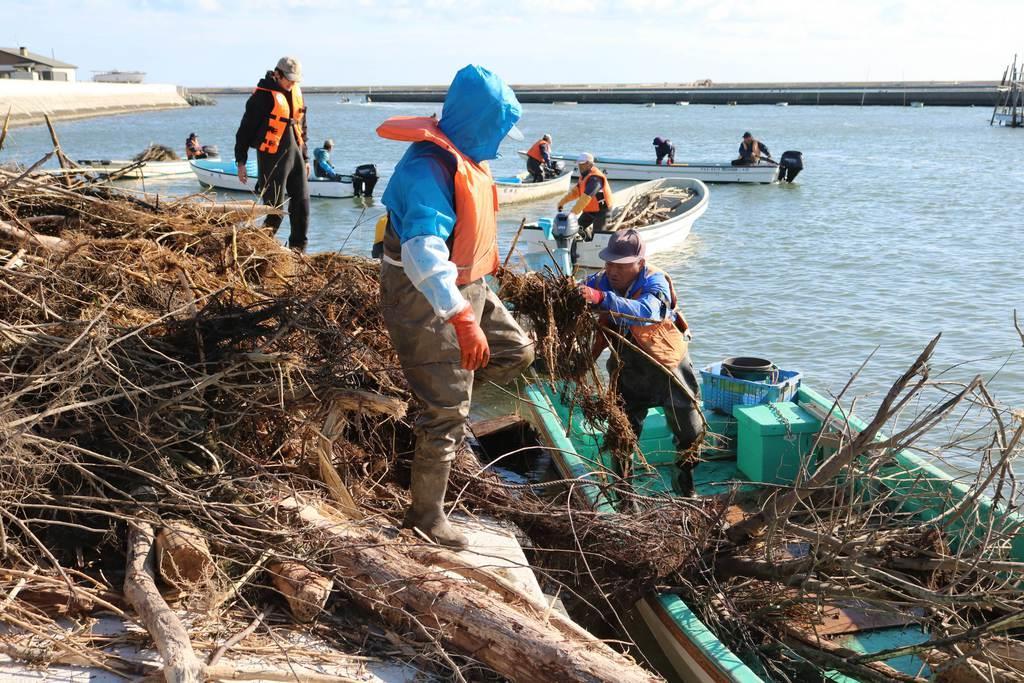 松川浦で回収したゴミを引き上げる漁業関係者=8日、福島県相馬市(芹沢伸生撮影)