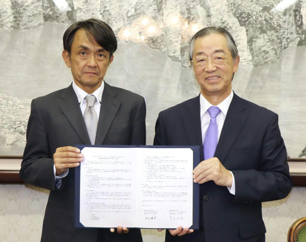 協定書に署名したJTAの青木紀将社長(左)と崇城大の中山峰男学長