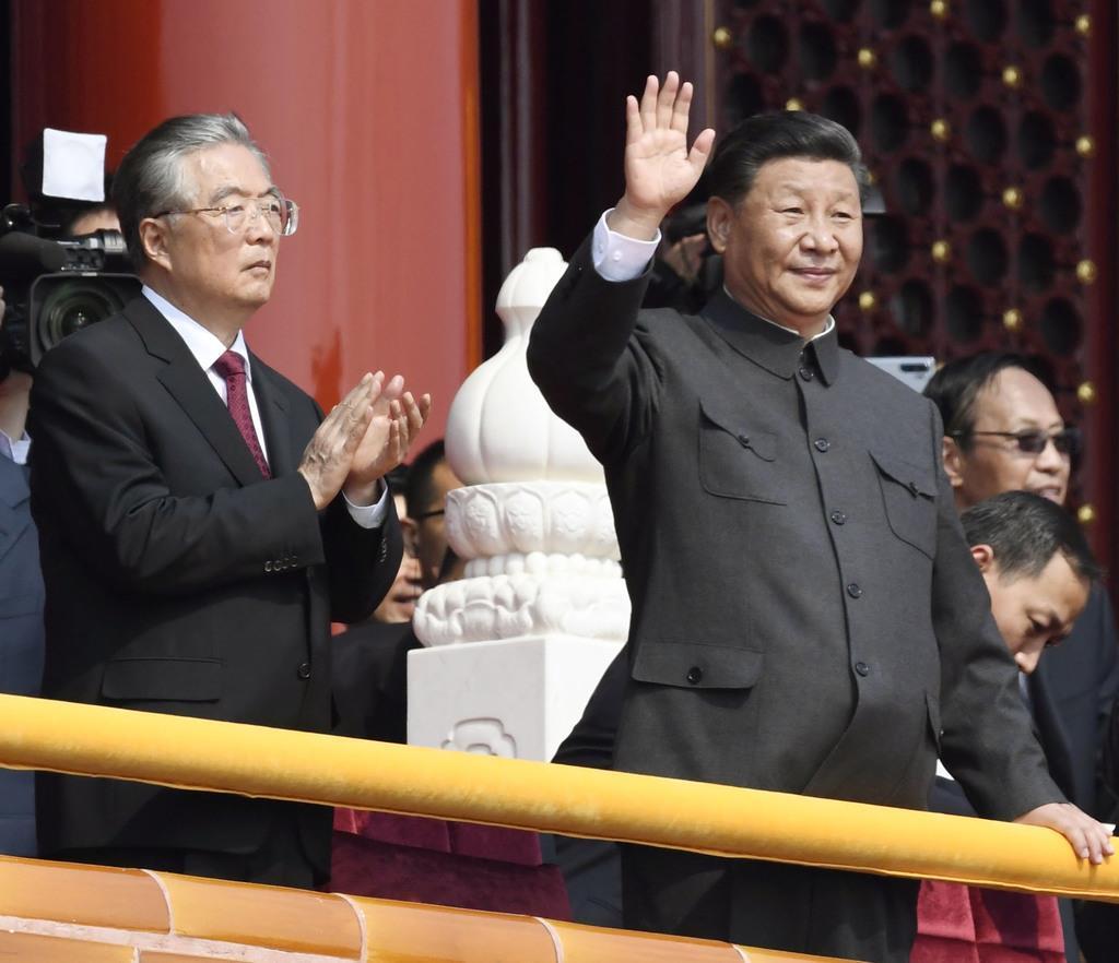 中国建国70年の記念式典で手を振る習近平国家主席。左は胡錦濤前国家主席=北京の天安門(共同)
