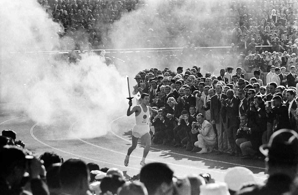 東京オリンピック五輪の開会式。聖火リレー最終ランナーの坂井義則さんが国立競技場に入り聖火台を目指した=昭和39年10月10日