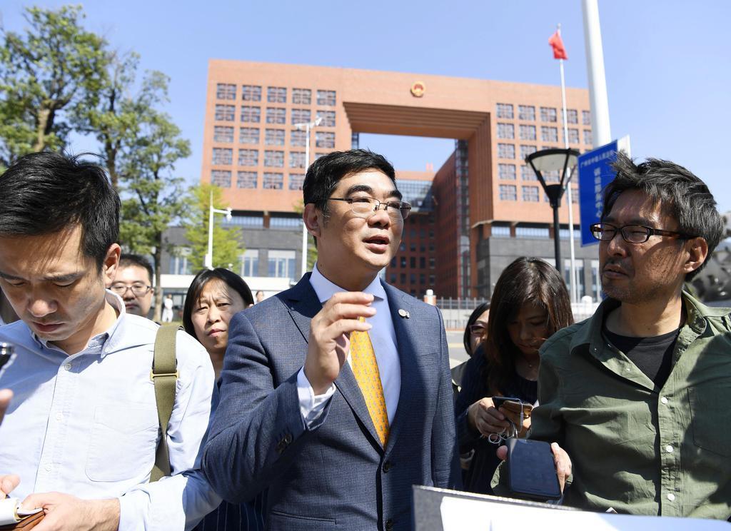 判決公判を終え、中国・広州市の中級人民法院(奥)を後にする桜木琢磨被告の弁護人(中央)=8日(共同)