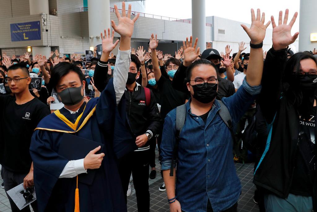 手を上げて追悼の意を示す香港科技大の卒業生たち=8日、同大(ロイター)