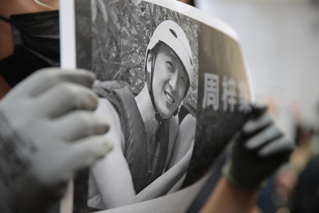 死亡した男子学生の写真を掲げる同大の学生たち=8日、香港(AP)