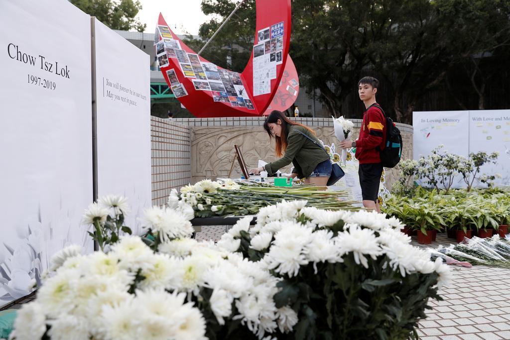 死を悼み、献花に訪れる学生たち=8日、香港科技大(ロイター)