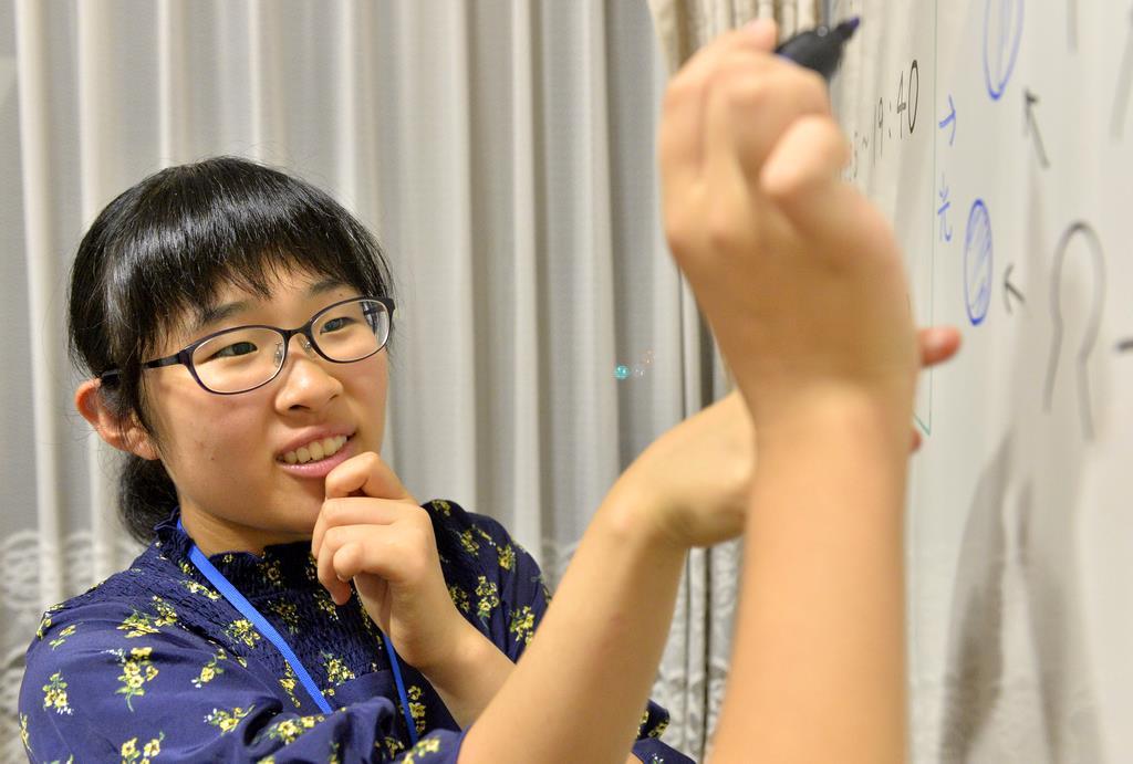 スタッフとして小学生に勉強を教えている小西珠生さん=28日午後、岡山市北区(須谷友郁撮影)