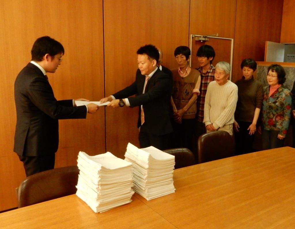 有効署名を添えて山田紘平町長(左)に高さ制限の条例制定を直接請求する町民ら=島本町役場