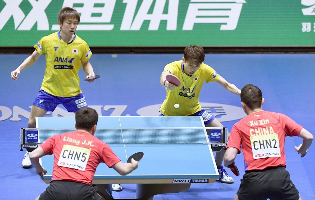 男子準決勝 中国戦の1試合目でプレーする丹羽(左)、吉村組=東京体育館