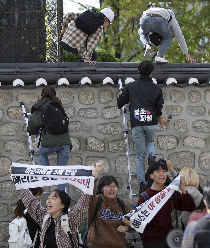 ソウルの米大使公邸にはしごを使って白昼侵入する学生ら=10月18日(ニューシス・AP)