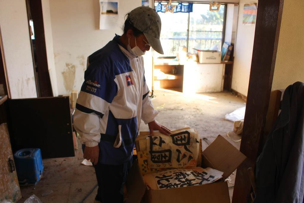 母が残した遺品を前に片付けの手を止める鈴木良子さん=福島県いわき市