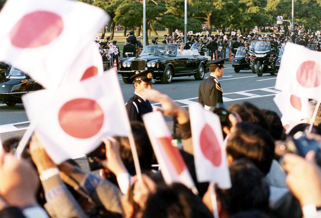 前回の「祝賀御列の儀」で、パレードされる上皇ご夫妻。沿道では多くの人が旗を振ってお迎えした=平成2年11月12日