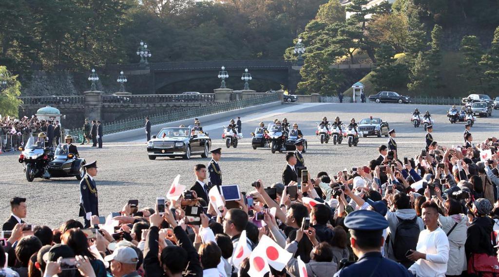 皇居前広場を通過する天皇、皇后両陛下を乗せたパレードの車列=10日午後、東京都千代田区(佐藤徳昭撮影)