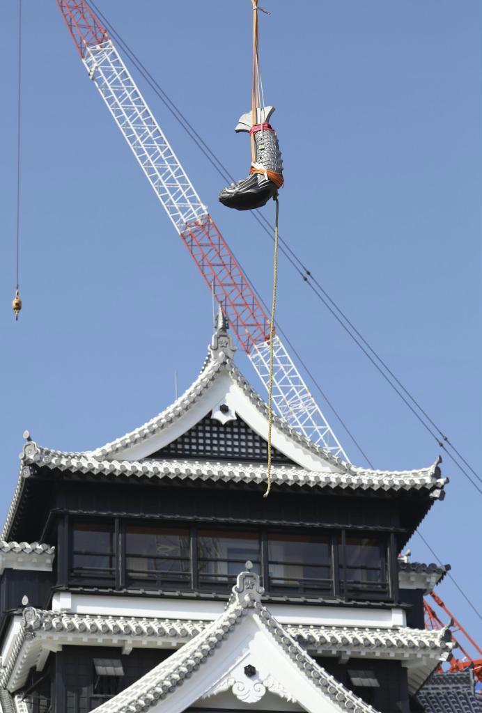 熊本城の大天守を背につり上げられるしゃちほこ=9日午前、熊本市