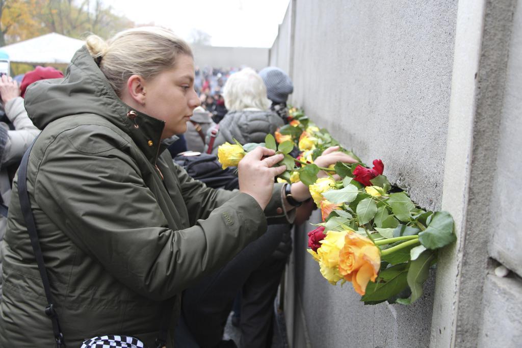 ベルリンの壁崩壊から30年を迎え、保存されている壁に献花する市民=9日、ベルリン(共同)
