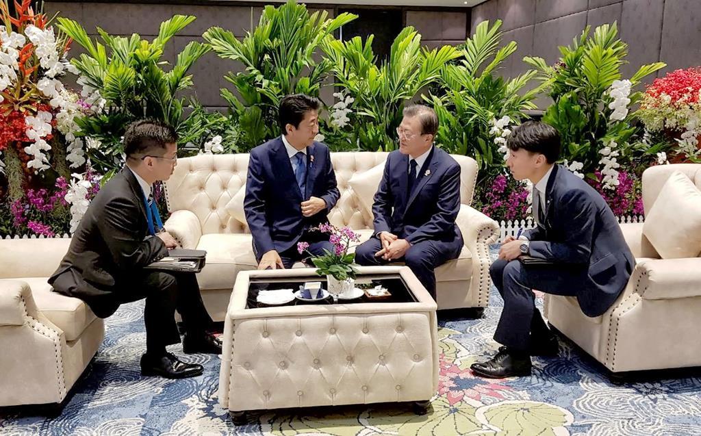 韓国の文在寅大統領と話す、ASEAN関連首脳会議に出席中の安倍晋三首相=4日、タイ・バンコク郊外(韓国大統領府提供・聯合=ロイター)
