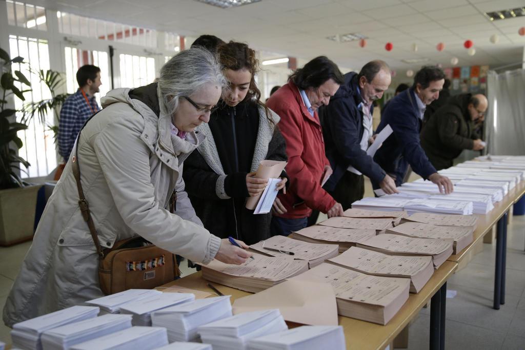 10日、スペインの首都マドリードで投票用紙を取る投票者(AP=共同)