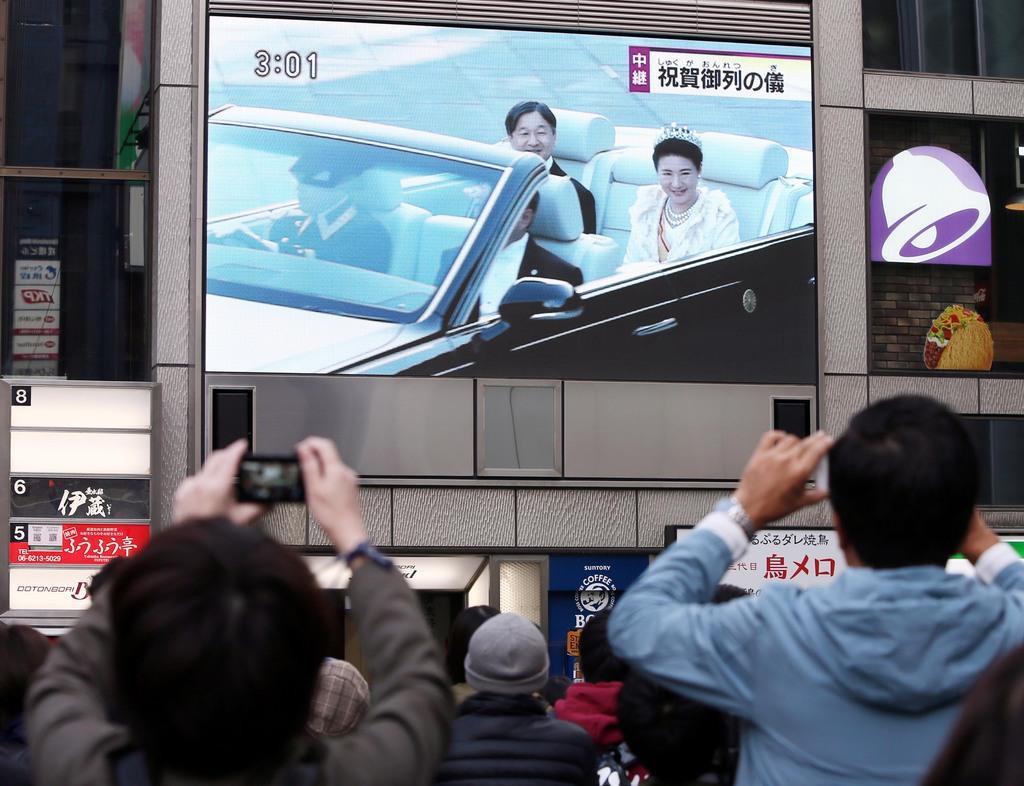 大阪・道頓堀の大型街頭ビジョンに映し出された祝賀御列の儀を足を止めて見る人たち=10日午後、大阪市中央区(前川純一郎撮影)