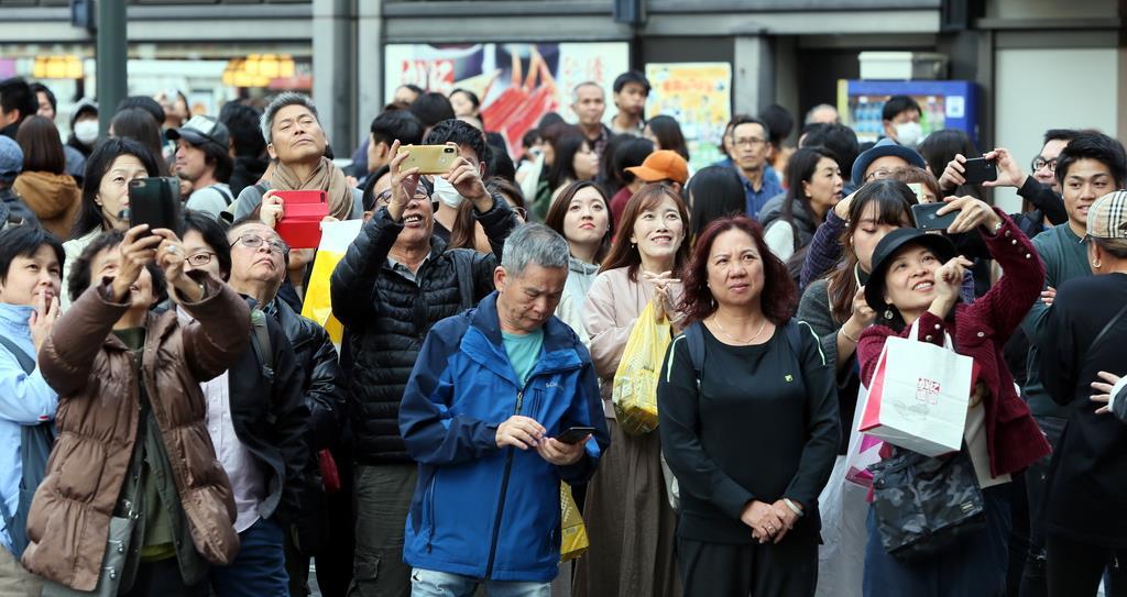 大阪・道頓堀の大型ビジョンに映し出された祝賀御列の儀を、足を止めて見る人たち=10日午後、大阪市中央区(前川純一郎撮影)