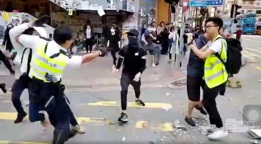 黒シャツとマスク姿の若者(中央)に銃を向ける警官=11日、香港(香港メディア「立場新聞」のウェブサイトより・共同)