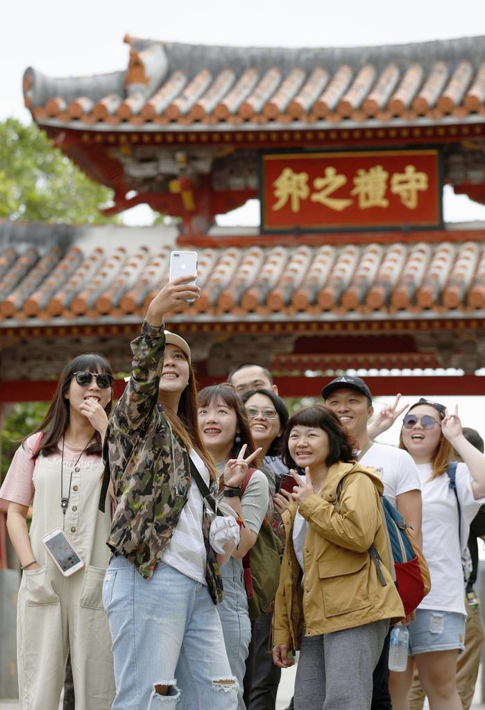 首里城の守礼門を訪れ記念撮影する台湾人観光客=1日、那覇市