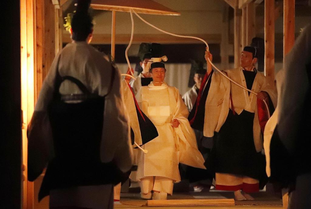 薄明かりの中、「悠紀殿供饌の儀」のため、祭服を着て悠紀殿に進まれる天皇陛下=14日午後6時35分、皇居・東御苑(代表撮影)