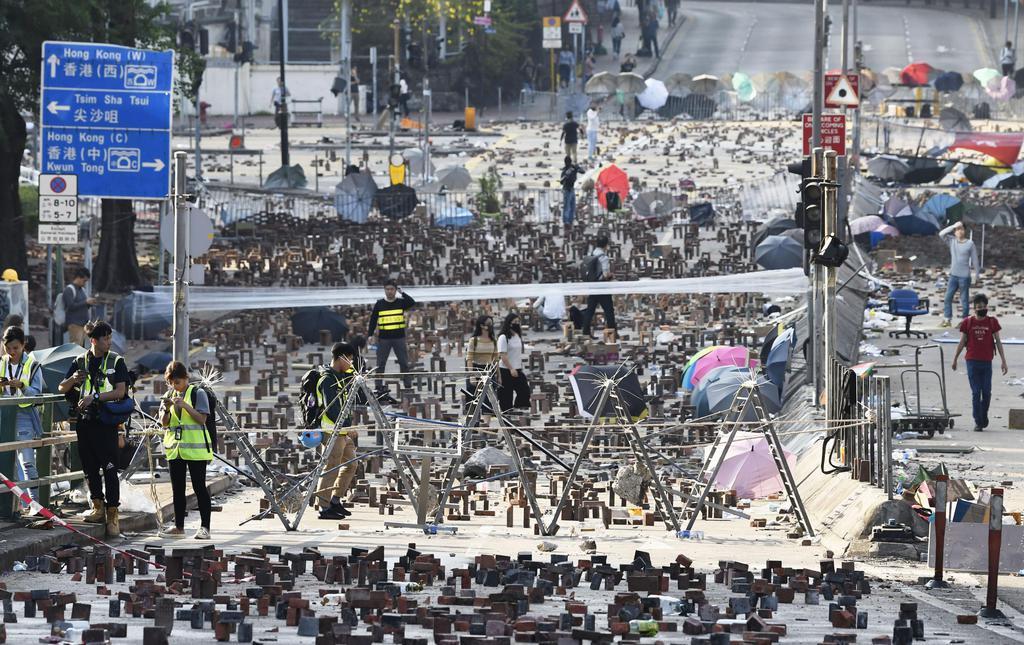 バリケードや障害物が置かれる香港理工大付近の道路=15日、香港(共同)