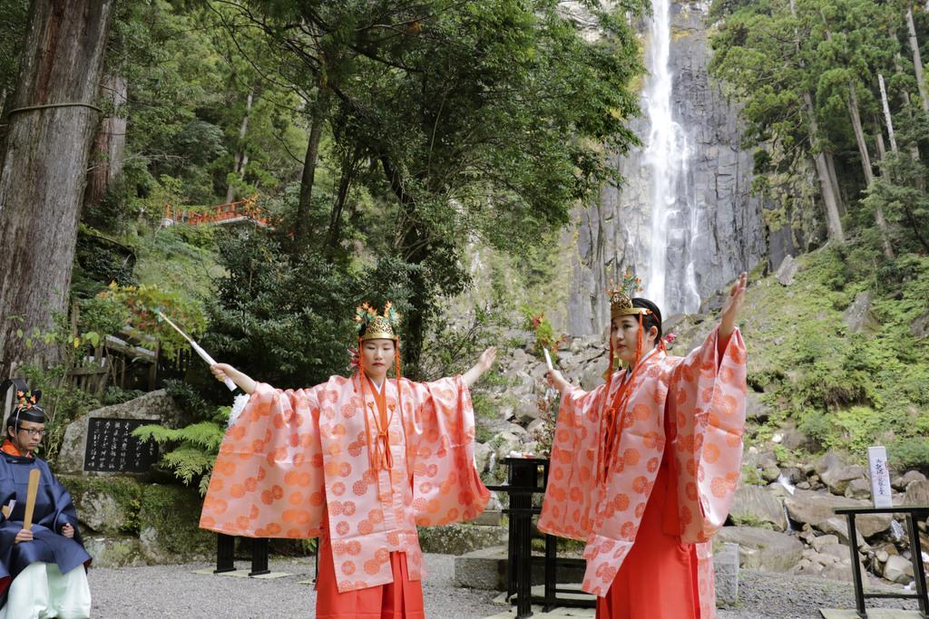 ご神体「那智の滝」前で神楽を披露する巫女(みこ) =14日、和歌山県那智勝浦町の熊野那智大社