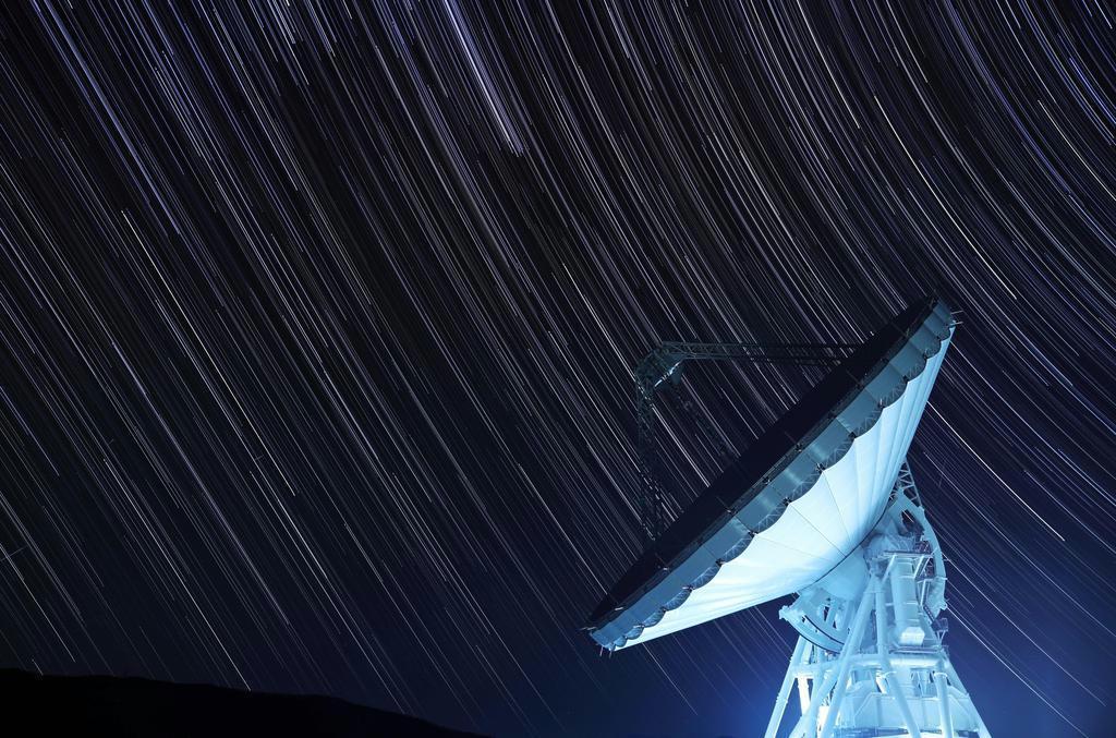 長時間露光を重ねた写真には、大型アンテナに降り注ぐように星の光跡が写った。まるで、はるかかなたの宇宙と対話をしているようだ =長野県佐久市