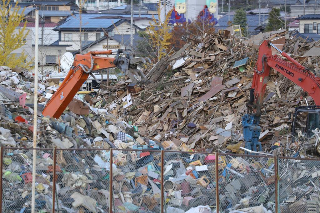 丸森町役場庁舎前は災害廃棄物の仮置き場となっており山積みになっていた=12日午前、宮城県丸森町(納冨康撮影)