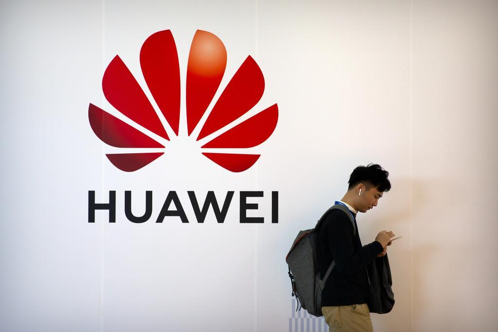 華為技術(ファーウェイ)の看板前で携帯電話を操作する男性=12日、北京(AP)