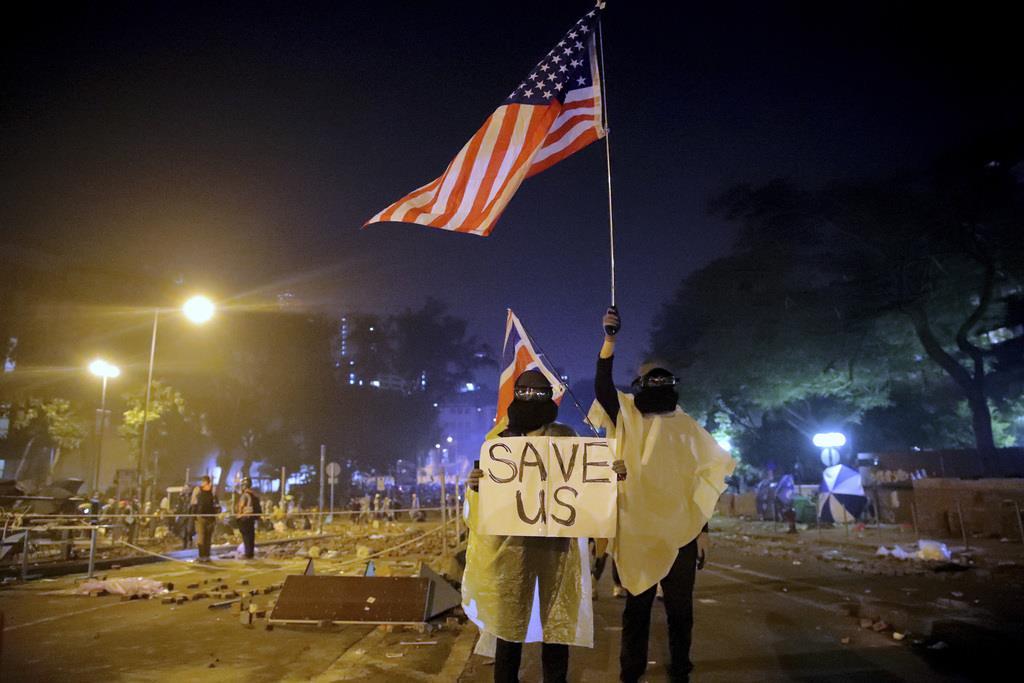「私たちを助けて」と書いたボードと米英の国旗を掲げる香港市民=18日(AP)