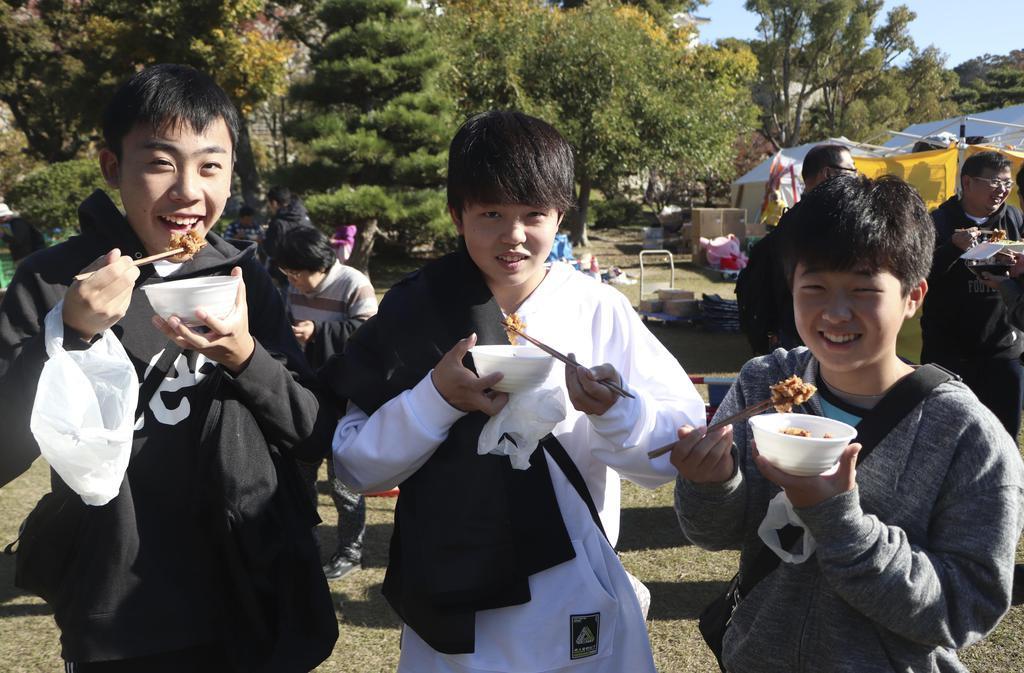 「第11回B-1グランプリ」で「高浜とりめし学会」の料理を楽しむ松本甲輝さん(左)ら=23日、兵庫県明石市