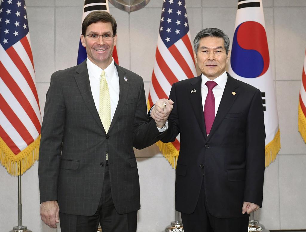 15日、米韓定例安保協議(SCM)の開催を前にソウル市内で握手するエスパー米国防長官(左)と韓国の鄭景斗国防相(共同)