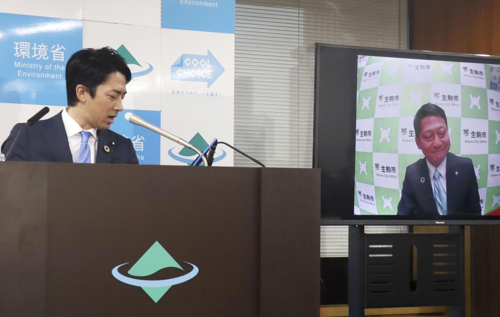 記者会見中に奈良県生駒市の小紫雅史市長(右)とインターネット電話「スカイプ」で会談する小泉環境相=26日午前、環境省