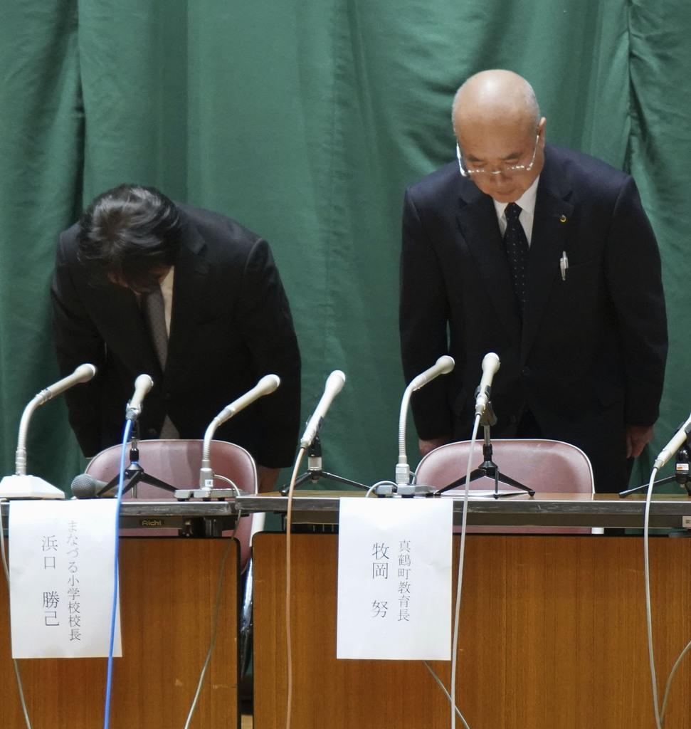 記者会見で頭を下げる牧岡努教育長(右)と、まなづる小学校の浜口勝己校長=26日午後、神奈川県真鶴町