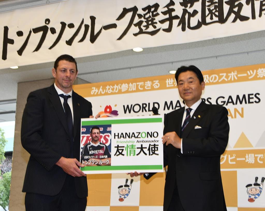 野田義和市長(右)から「花園友情大使」の名刺を手渡されたトンプソン・ルーク選手=大阪府東大阪市役所