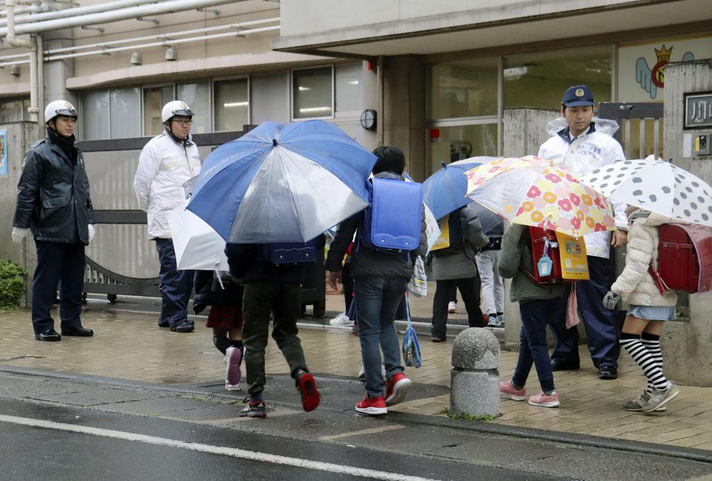 川崎市多摩区の小学校の正門前で、登校する児童を見守る警察官=27日午前8時ごろ